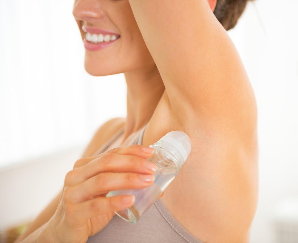 Closeup on happy young woman applying deodorant on underarm