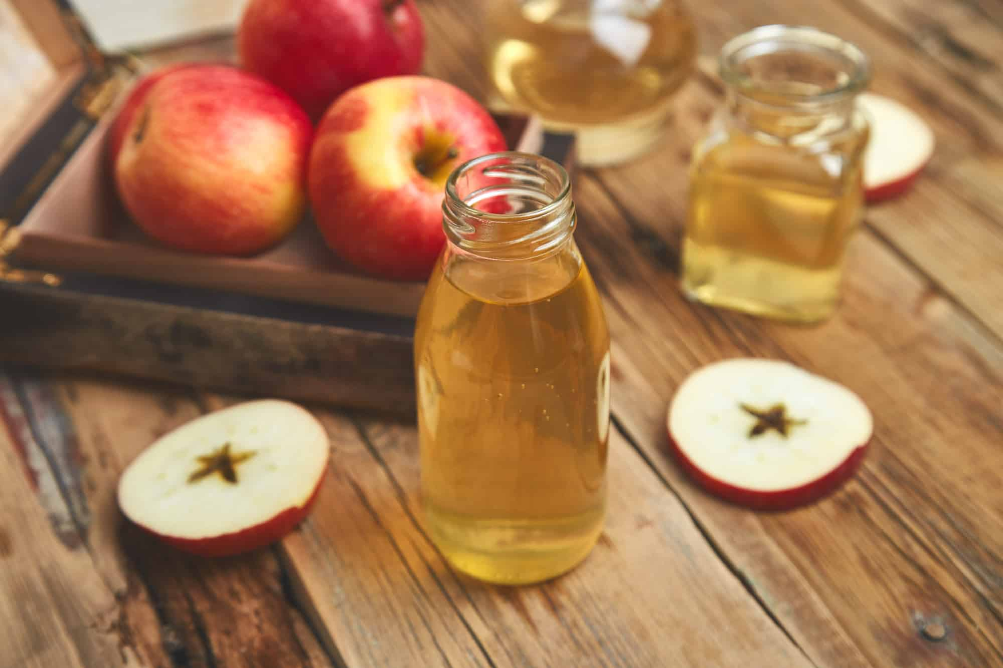 Apple cider vinegar. Glass Bottle of apple organic vinegar on wooden table. Healthy organic drink food. Bottle of fresh cider near autumn red apples. Rustic background