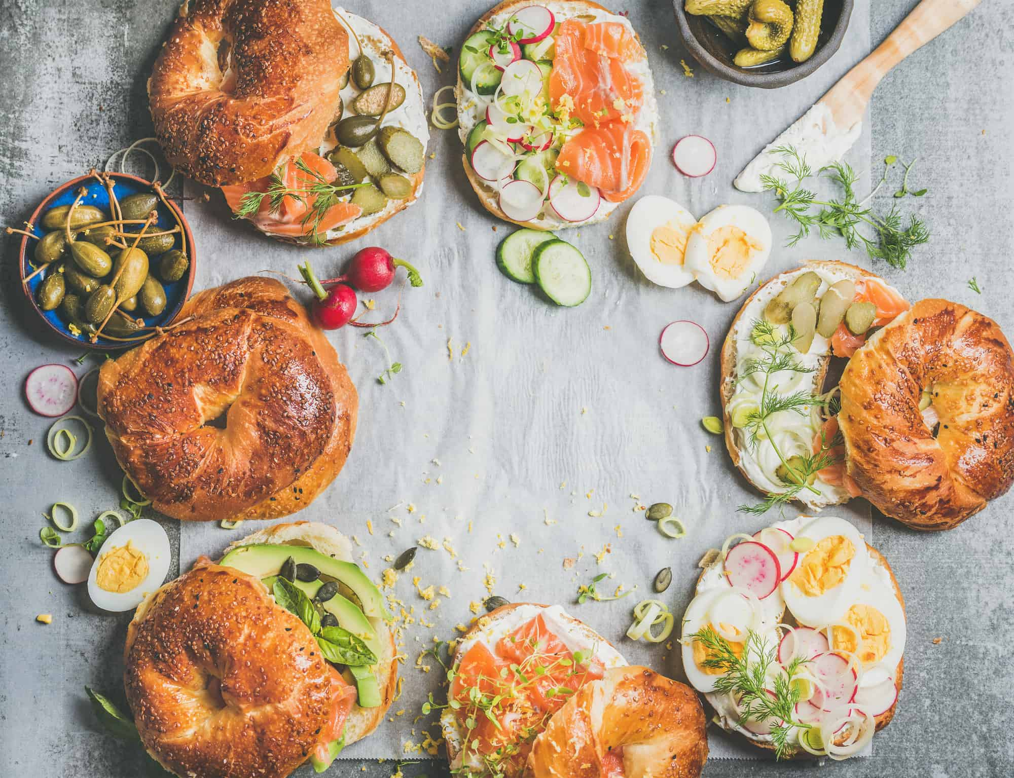 Variety of bagels with salmon, eggs, radish, avocado, cucumber, greens and cream cheese