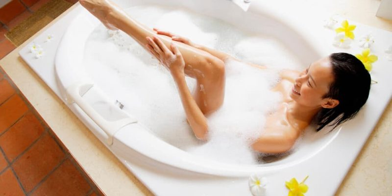 photo of woman sitting in a white bubbly bathtub