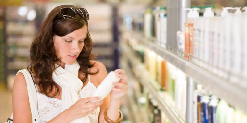 photo of woman reading ingredient label on shampoo bottle