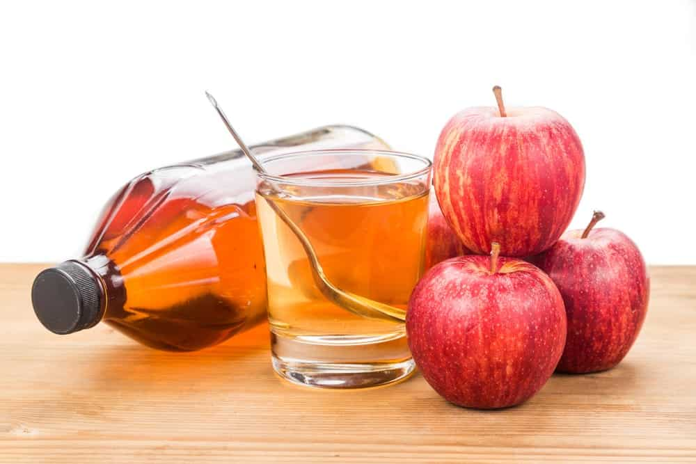 photo of apple cider vinegar in a bottle, glass, and apples stacked