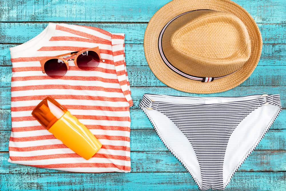 bikini oxybenzone sunscreen & sunglasses on teal wood board