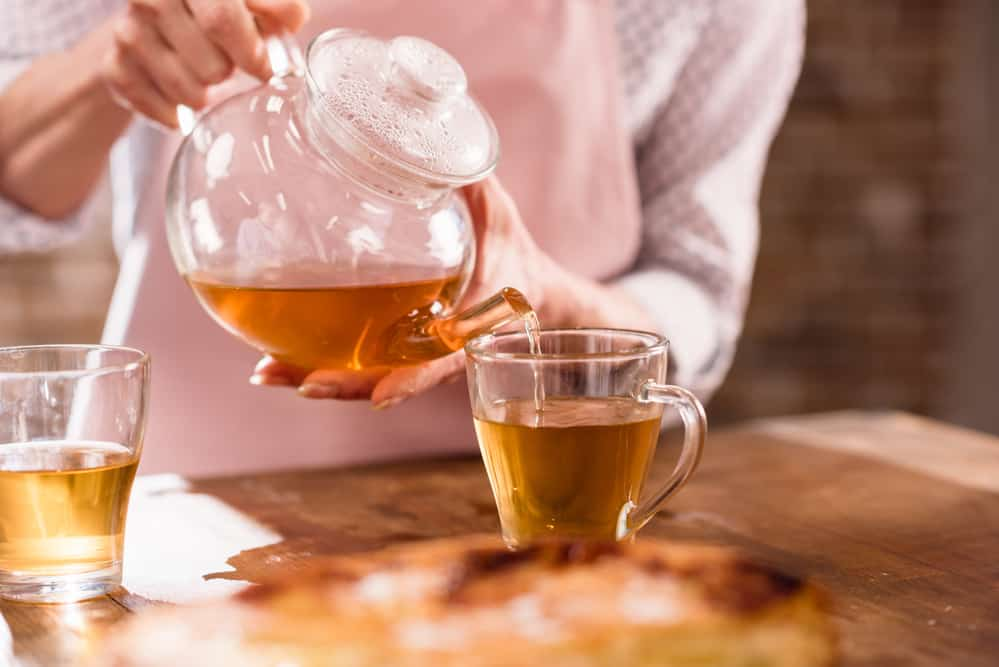 woman pouring tea from glass tea pot