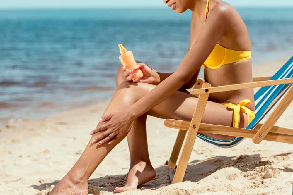woman putting on oxybenzone sunscreen on her leg in a bikini on the beach