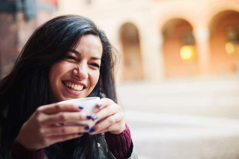 Smiling woman drinking tea in a cafe outdoors