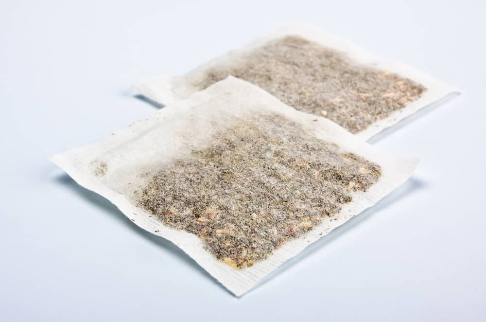 herbal tea bags laying on table, blue background