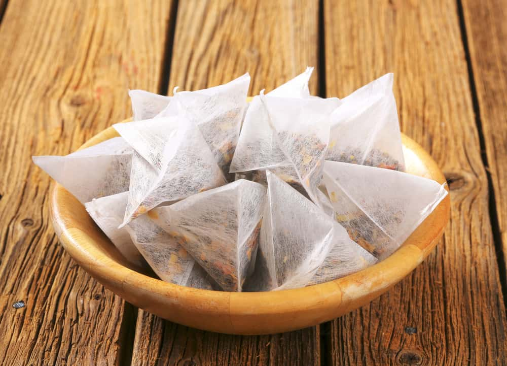 Pyramid-shaped jasmine tea bags in wooden bowl