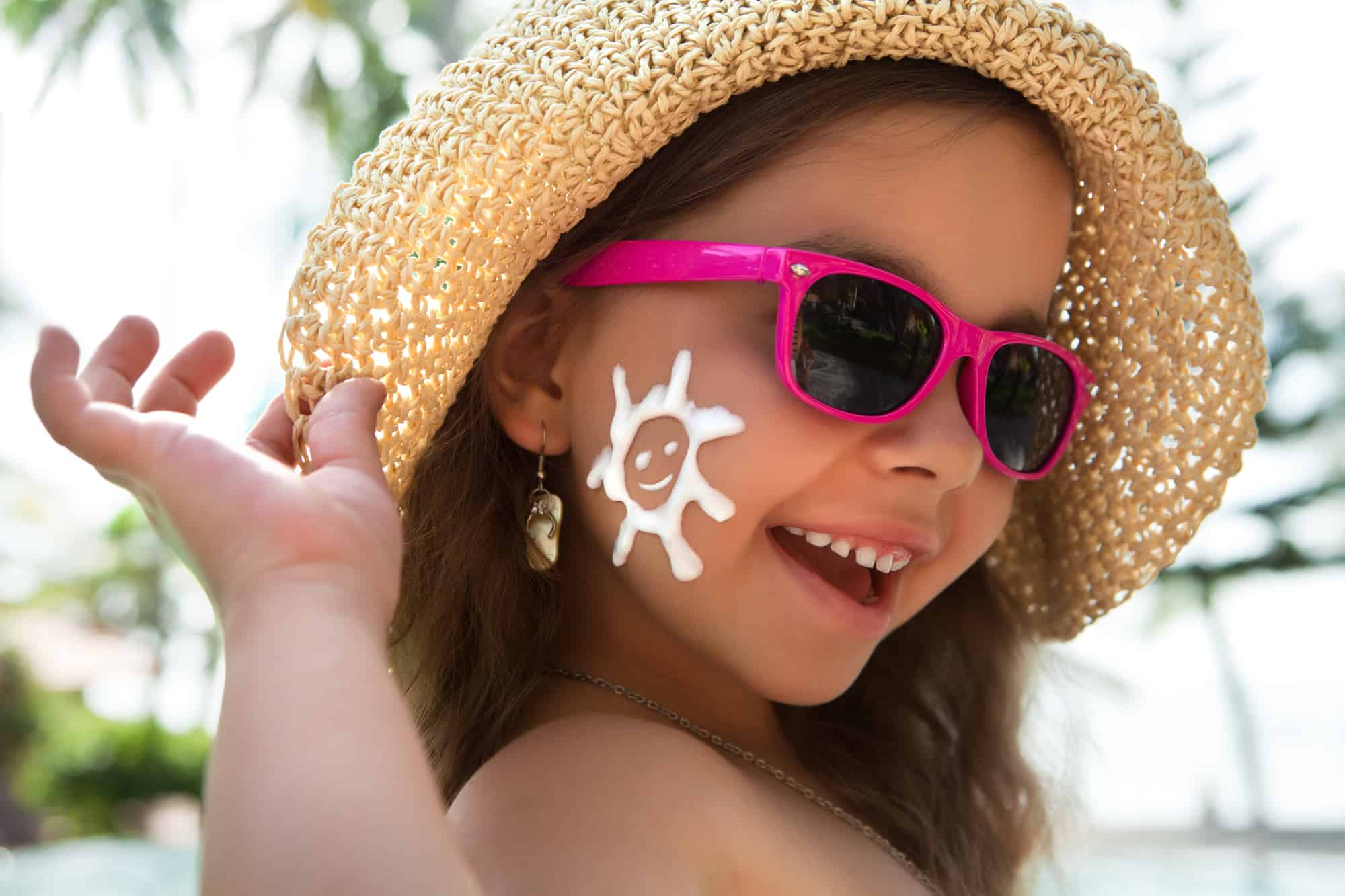 adorable little girl in a hat with sunglasses and sunscreen
