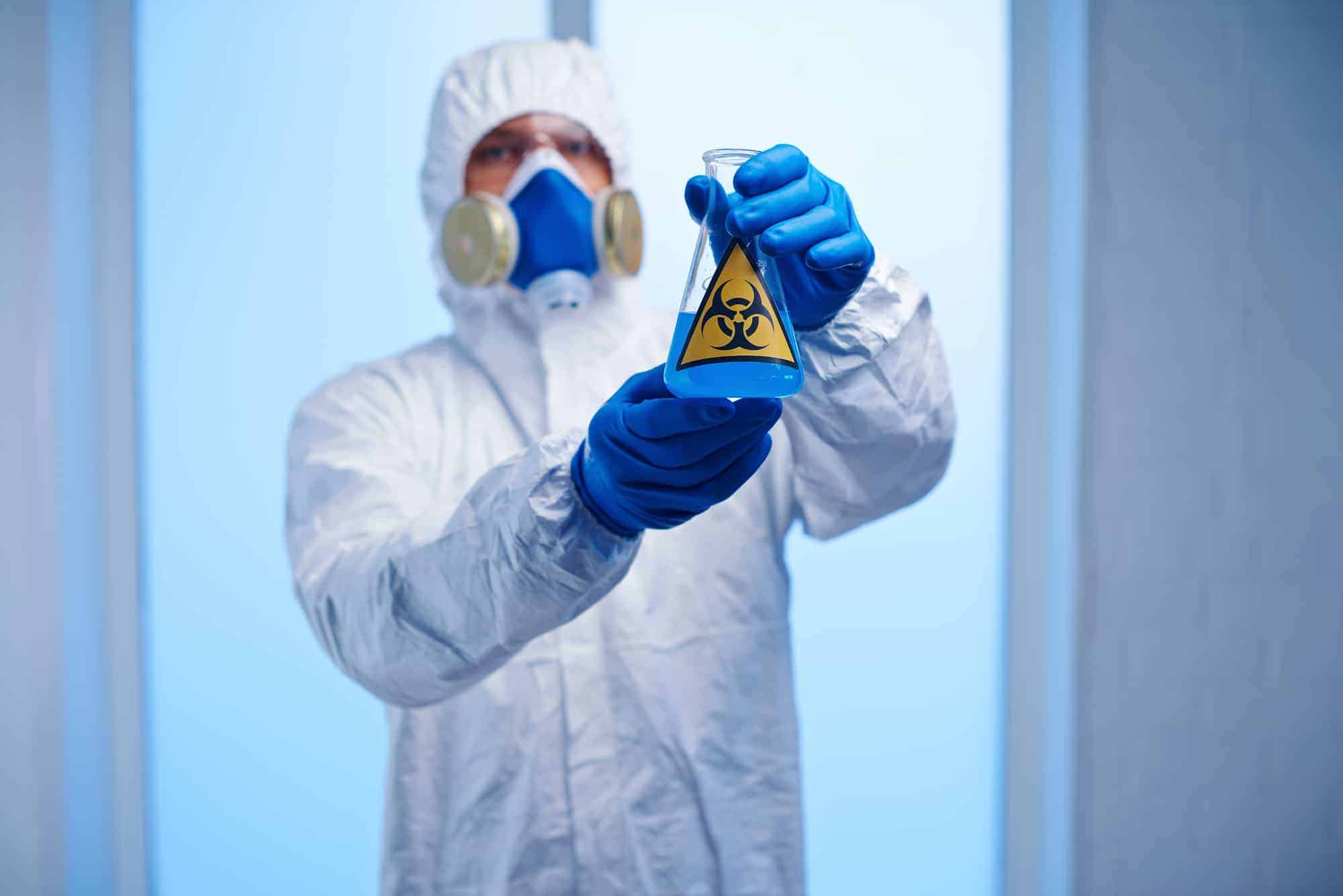 Chemist in protective outfit handling glyphosate