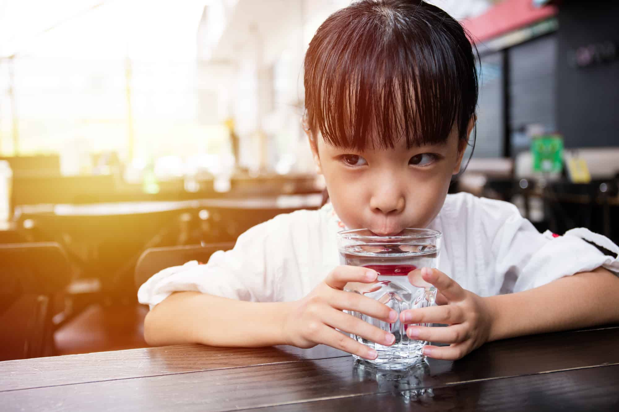girl drinking water in outdoor cafe