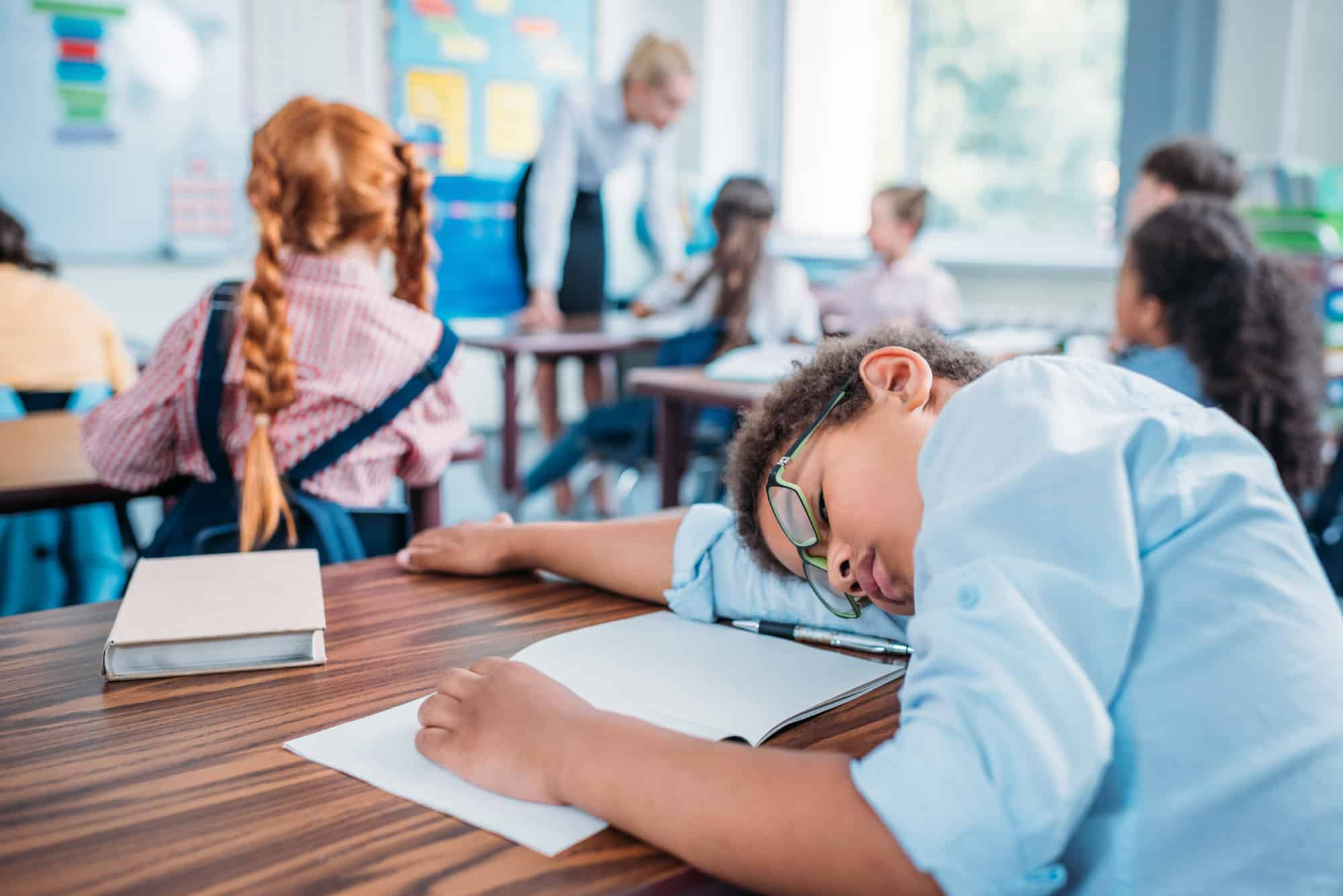 young boy fallen asleep in class with his head on the desk