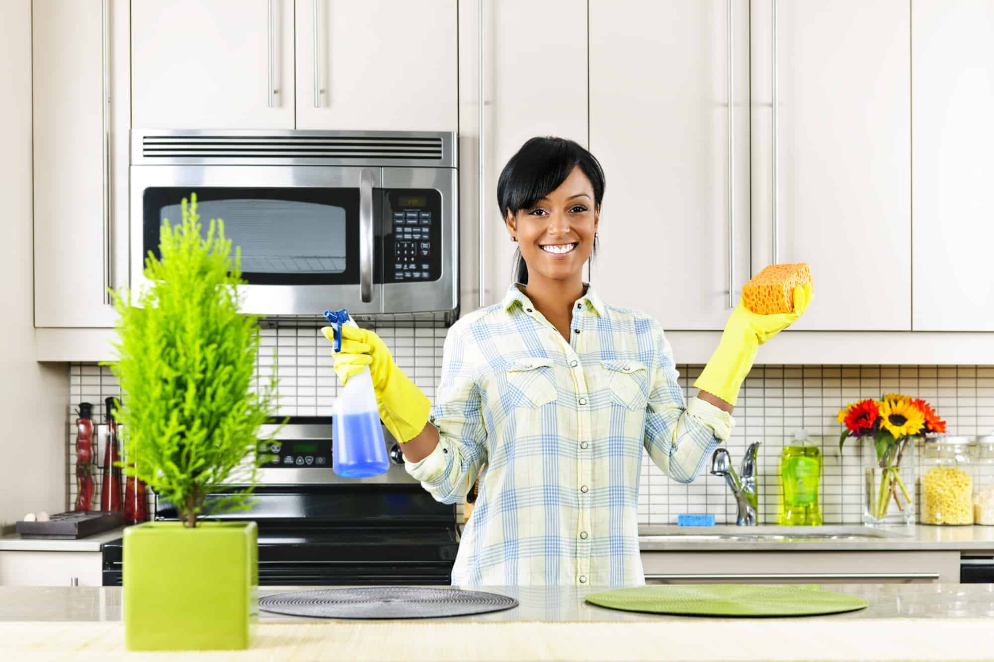 young black woman cleans kitchen with non-toxic cleaner