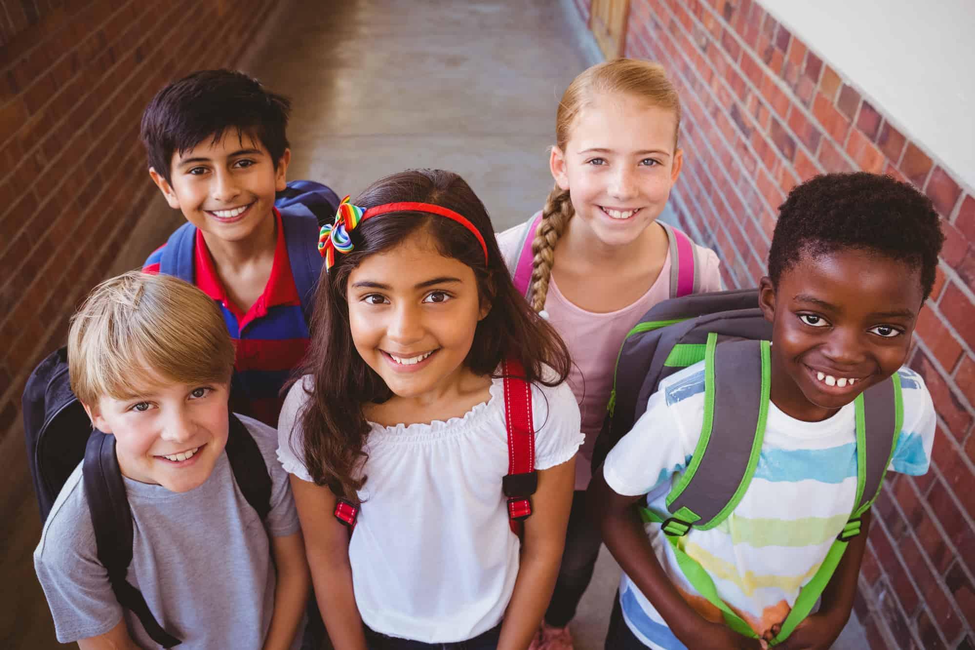 children smiling in corridor at school