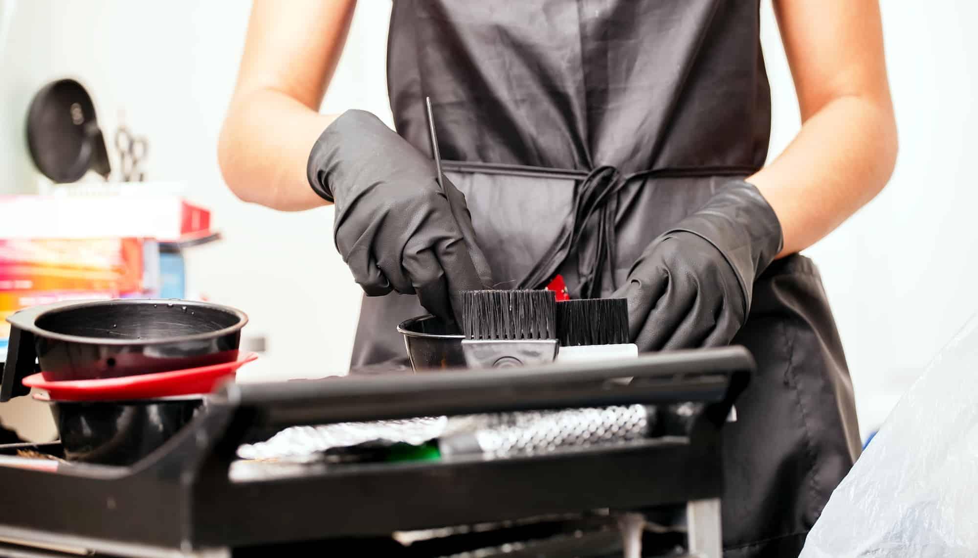 girl in black gloves hairdresser mixes hair dye