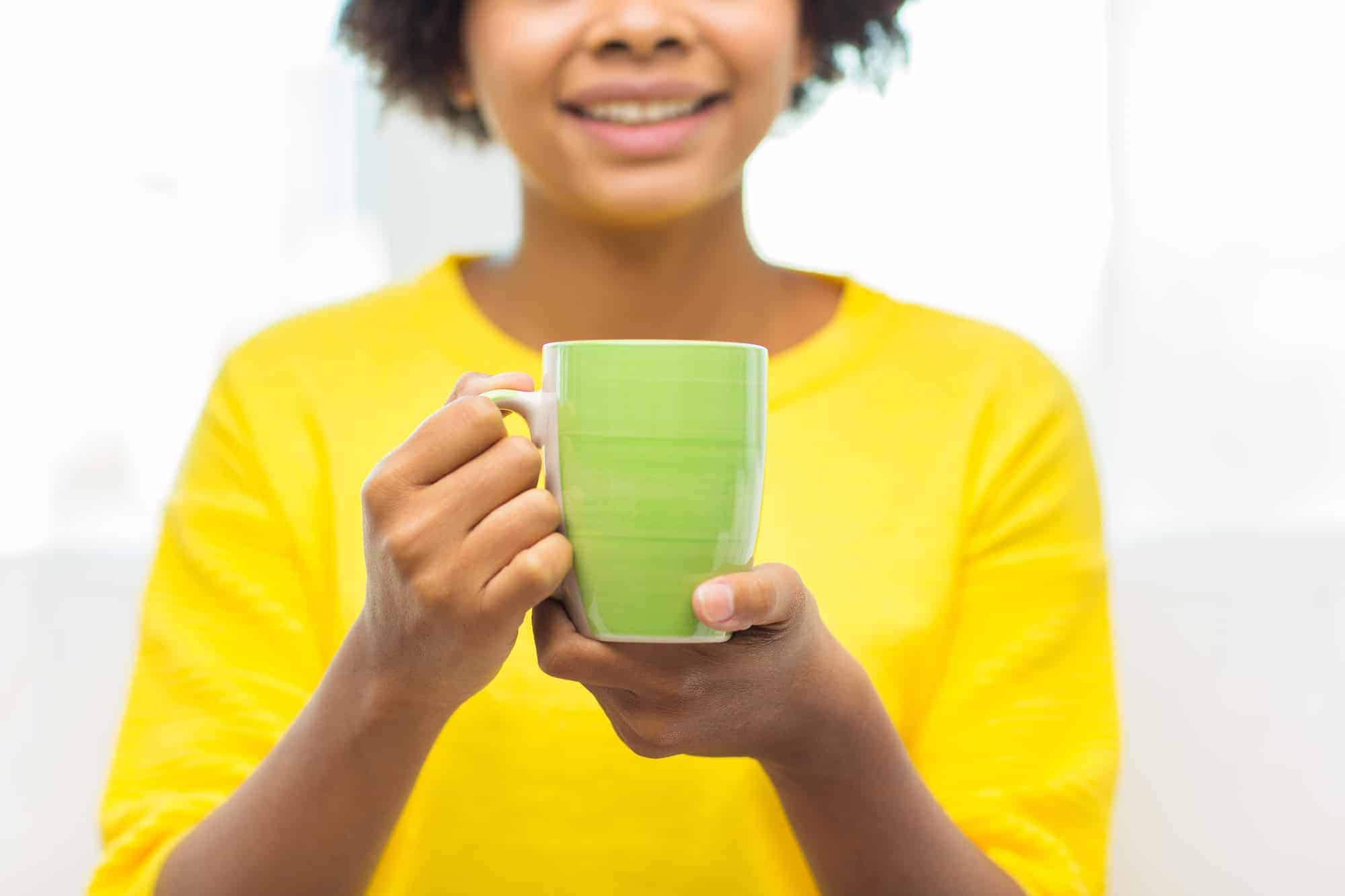 black woman holding a cup of tea in a green mug