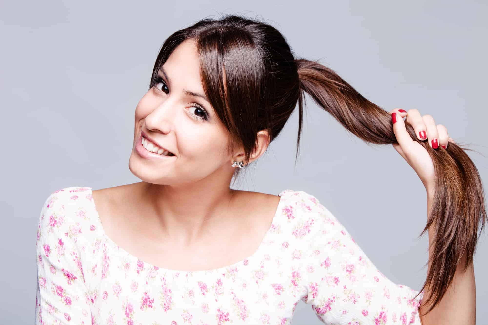 smiling girl hold her long shiny hair