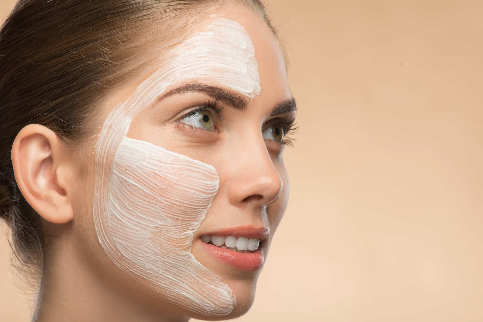 Close-up Portrait of beautiful smiling girl in spa with cosmetic cream on her face with clean and fresh skin looking aside