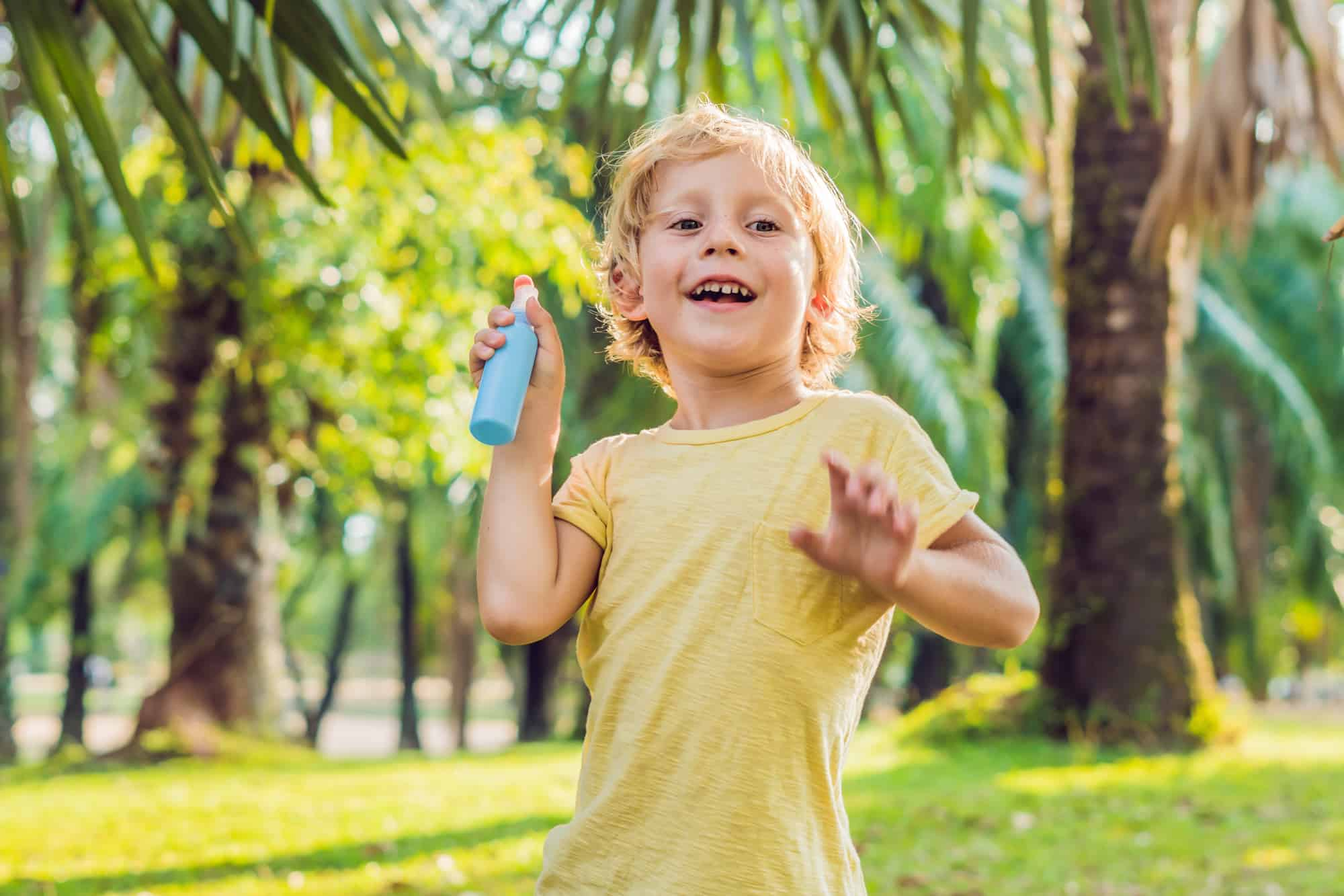 Boy spraying insect repellents on skin in the park