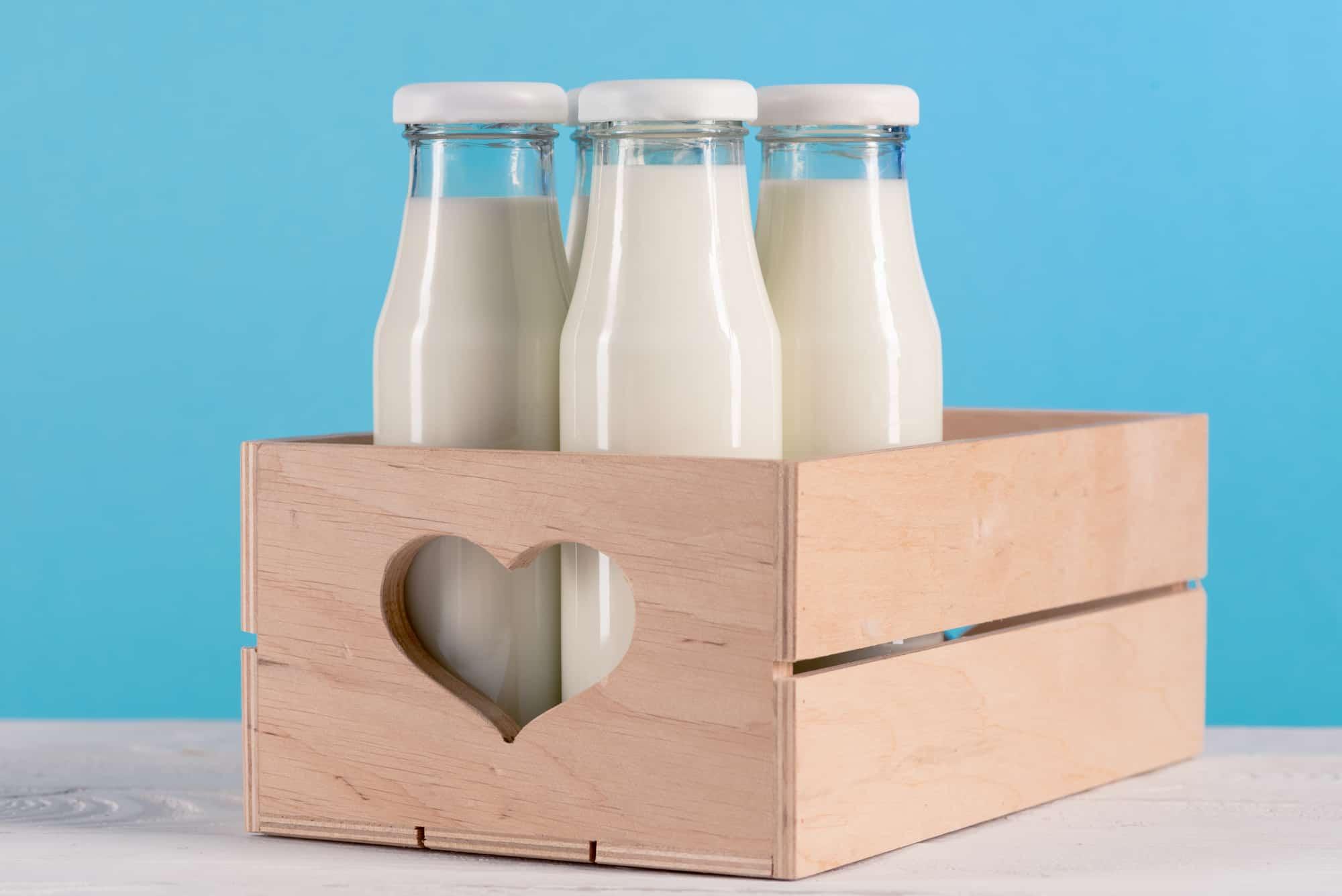 three milk jugs in a wooden box