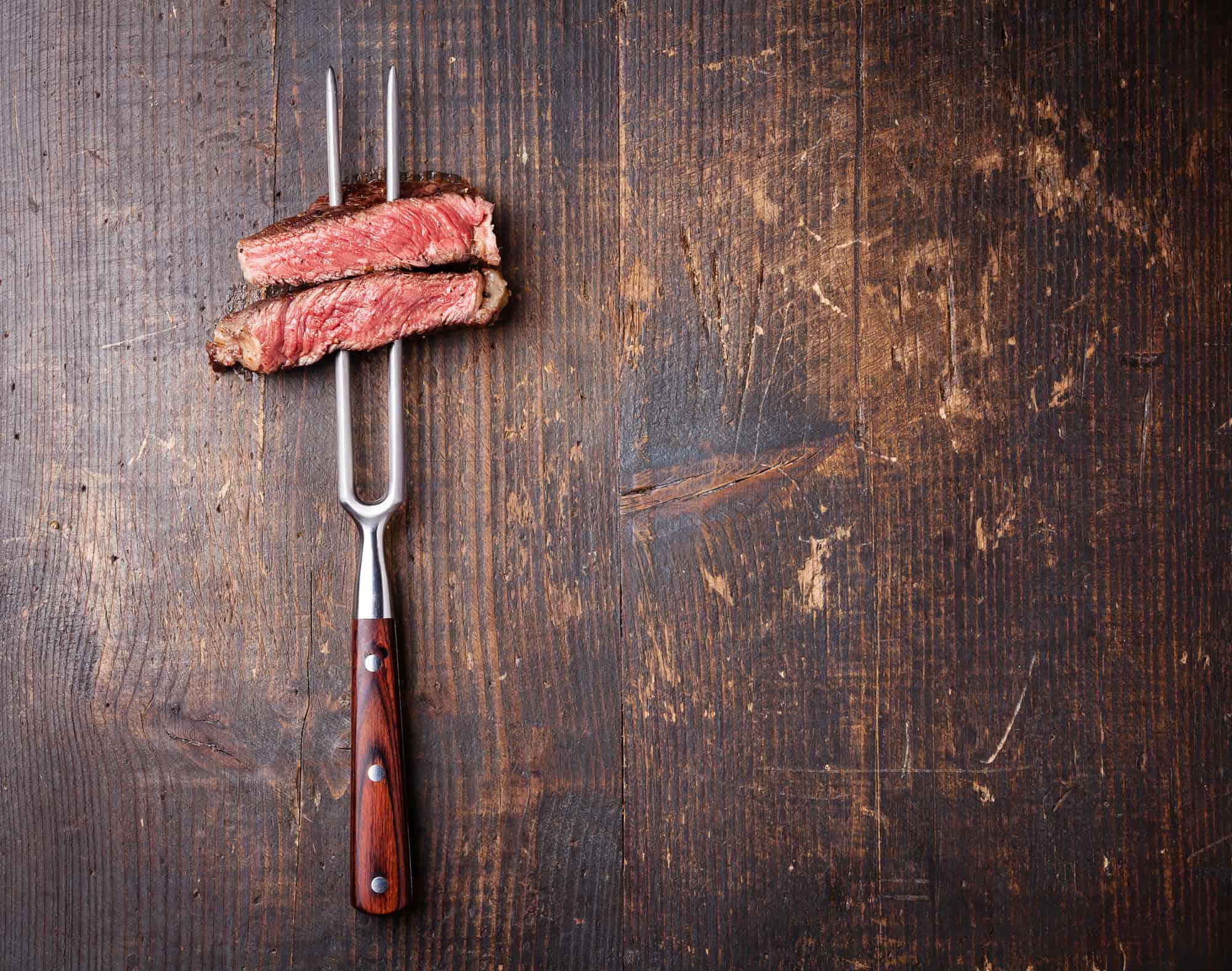 Slices of beef steak on meat fork on dark on wood