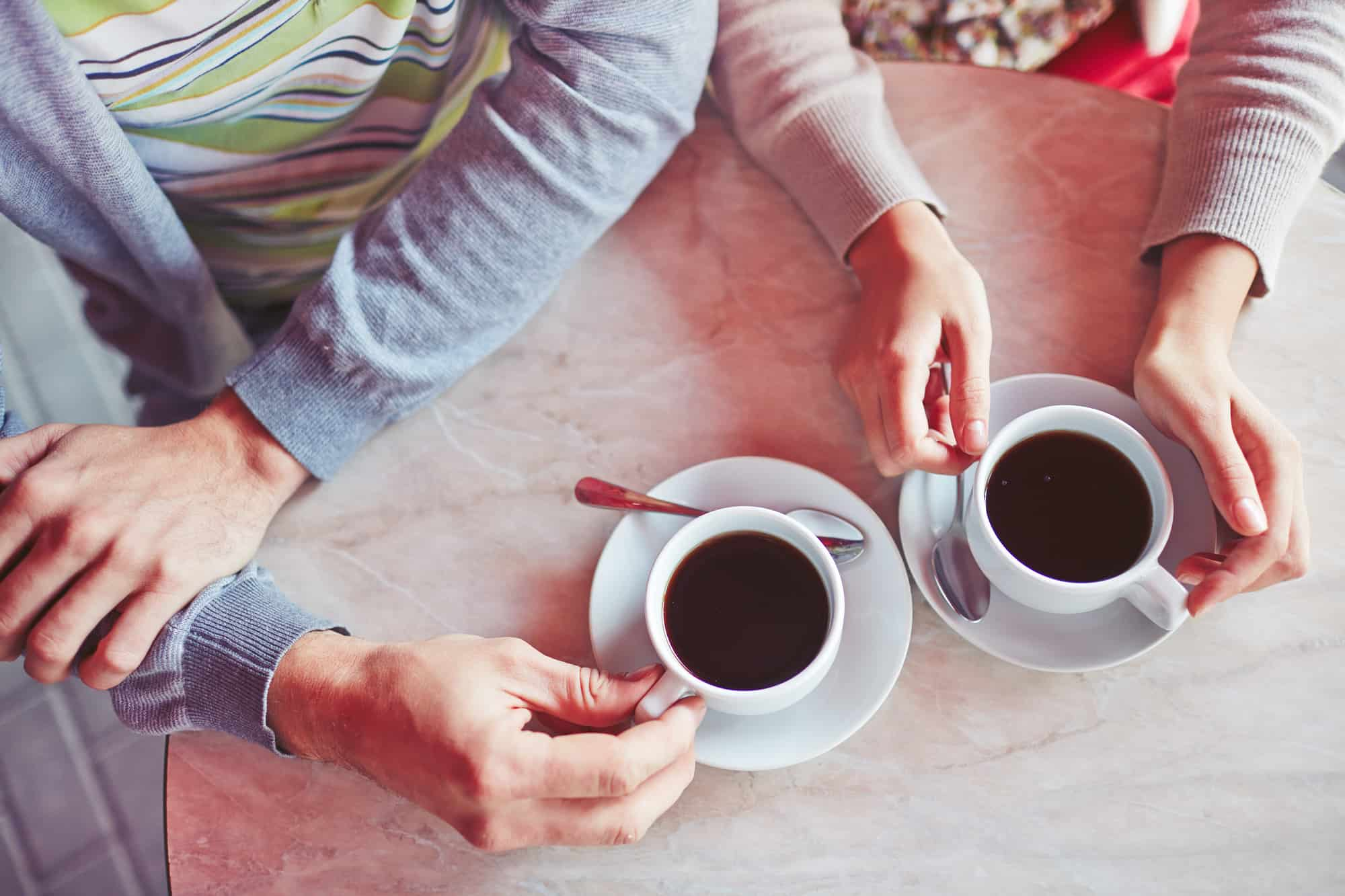 Close up of table and hands of young couple enjoying a cup of coffee at sidewalk restaurant