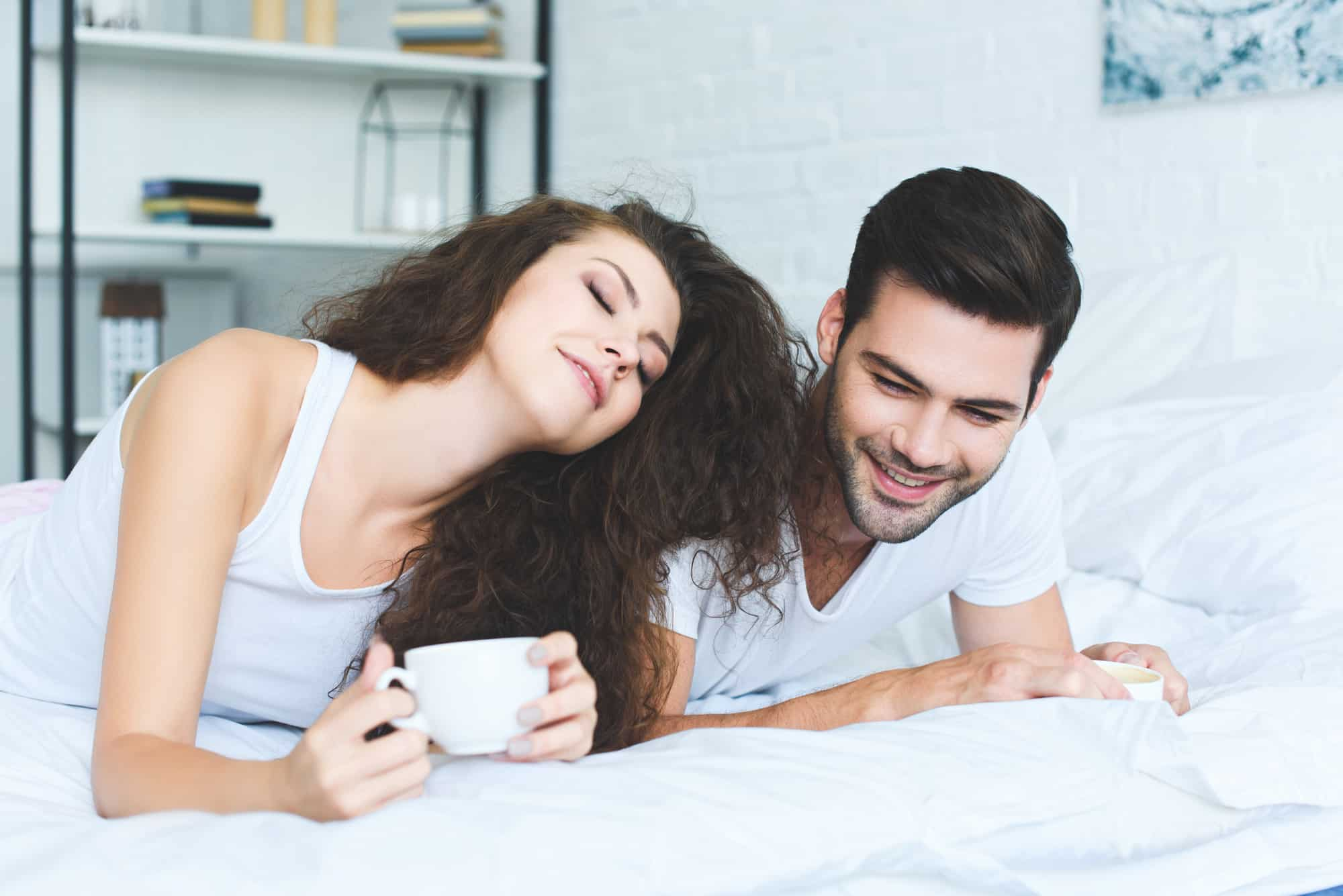 woman and man on the bed enjoying organic coffee