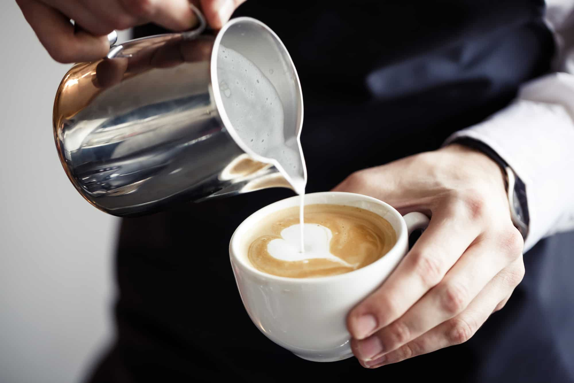 Man pouring creamy froth into coffee cup