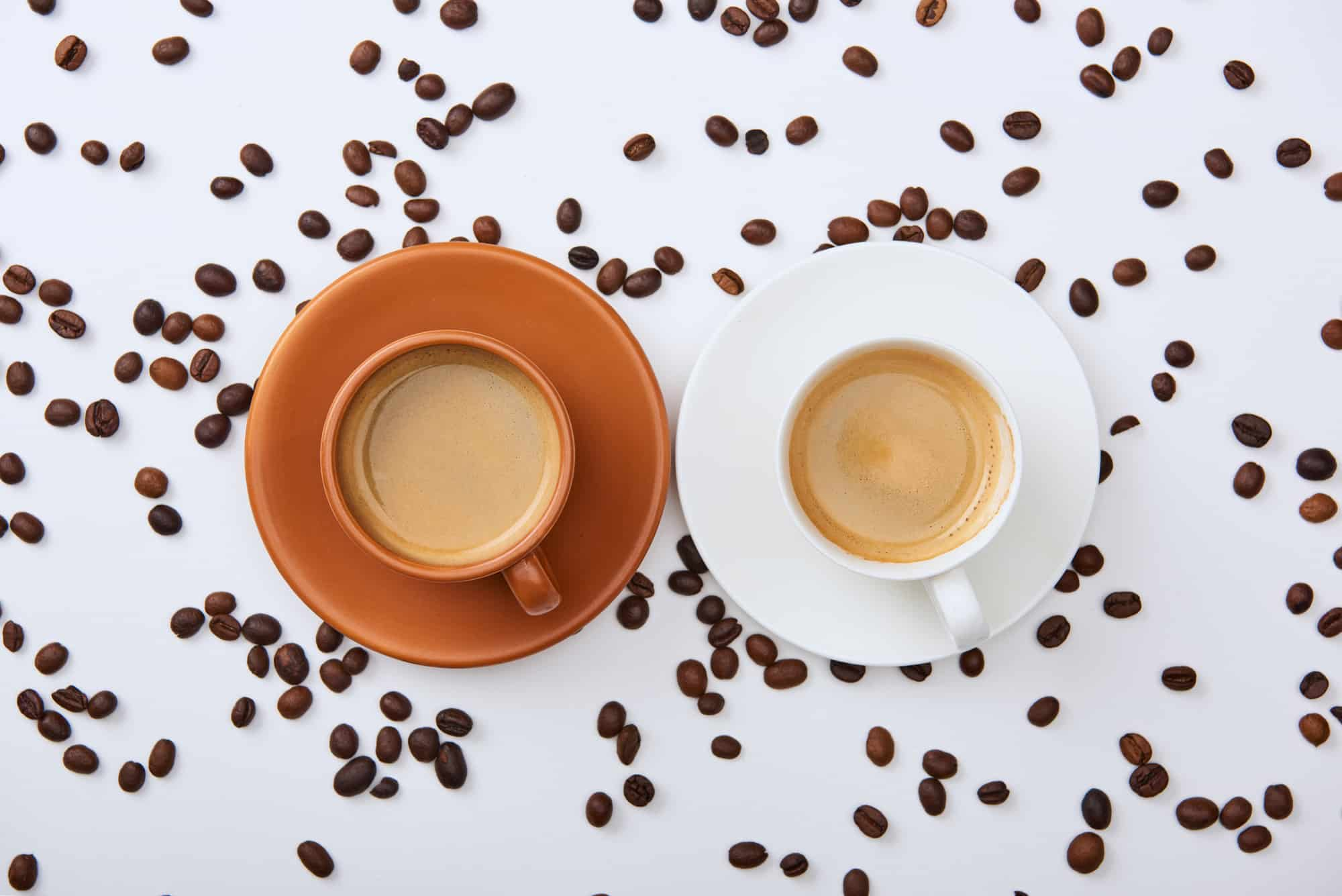 two cups of coffee side by side with cream against coffee beans