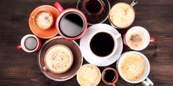 Many different cups of coffee on dark wooden table