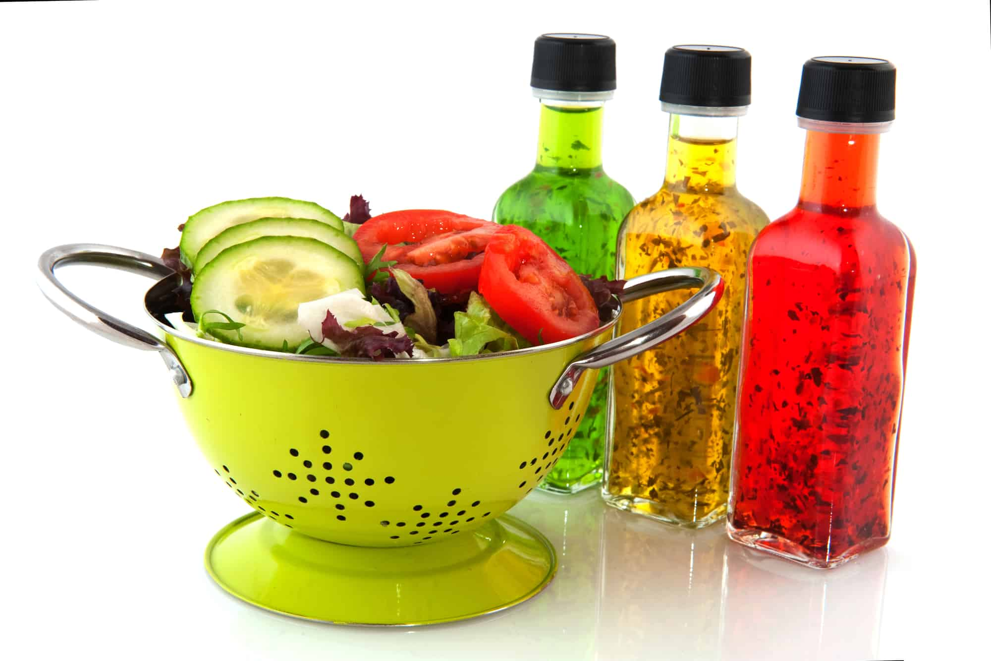 Colorful dressing with herbs in glass bottles