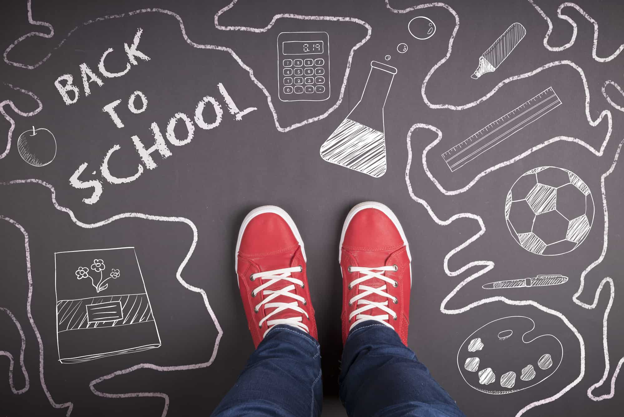 red shoes with white laces on chalkboard saying back to school