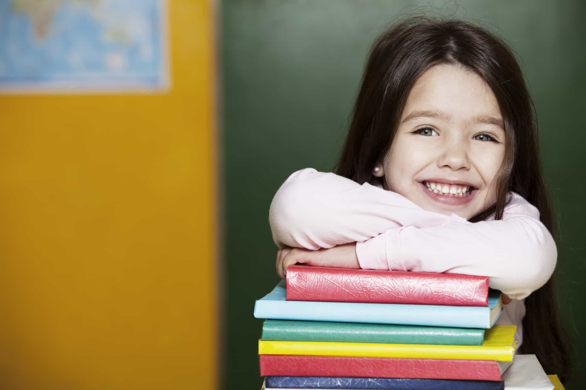young burnette girl resting on a pile of colorful books smiling