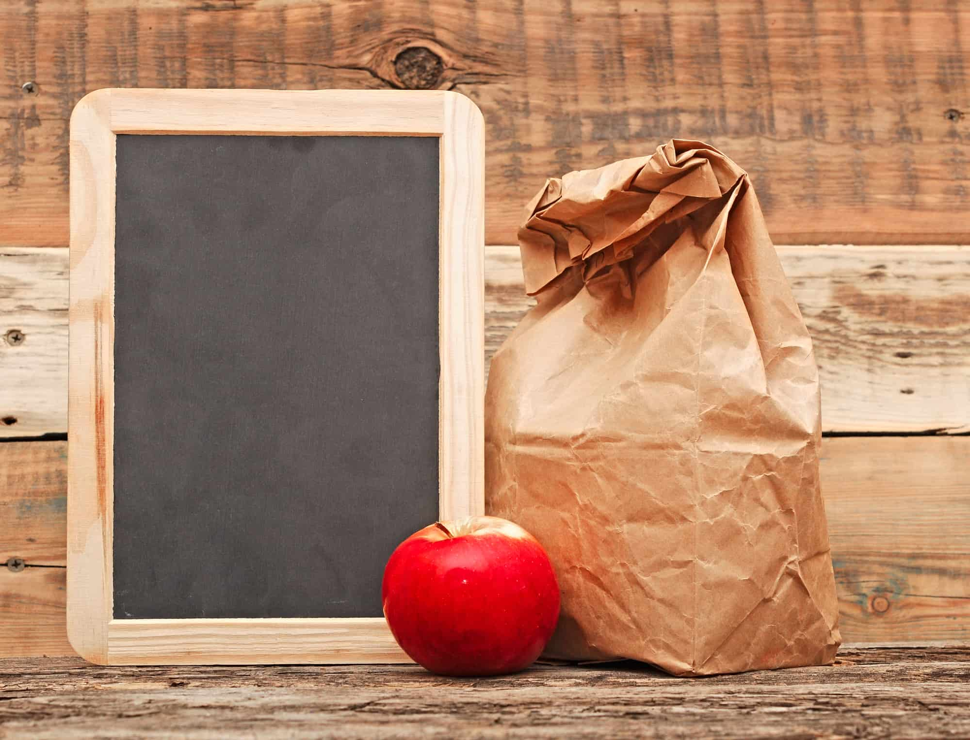 brown paper bag with apple