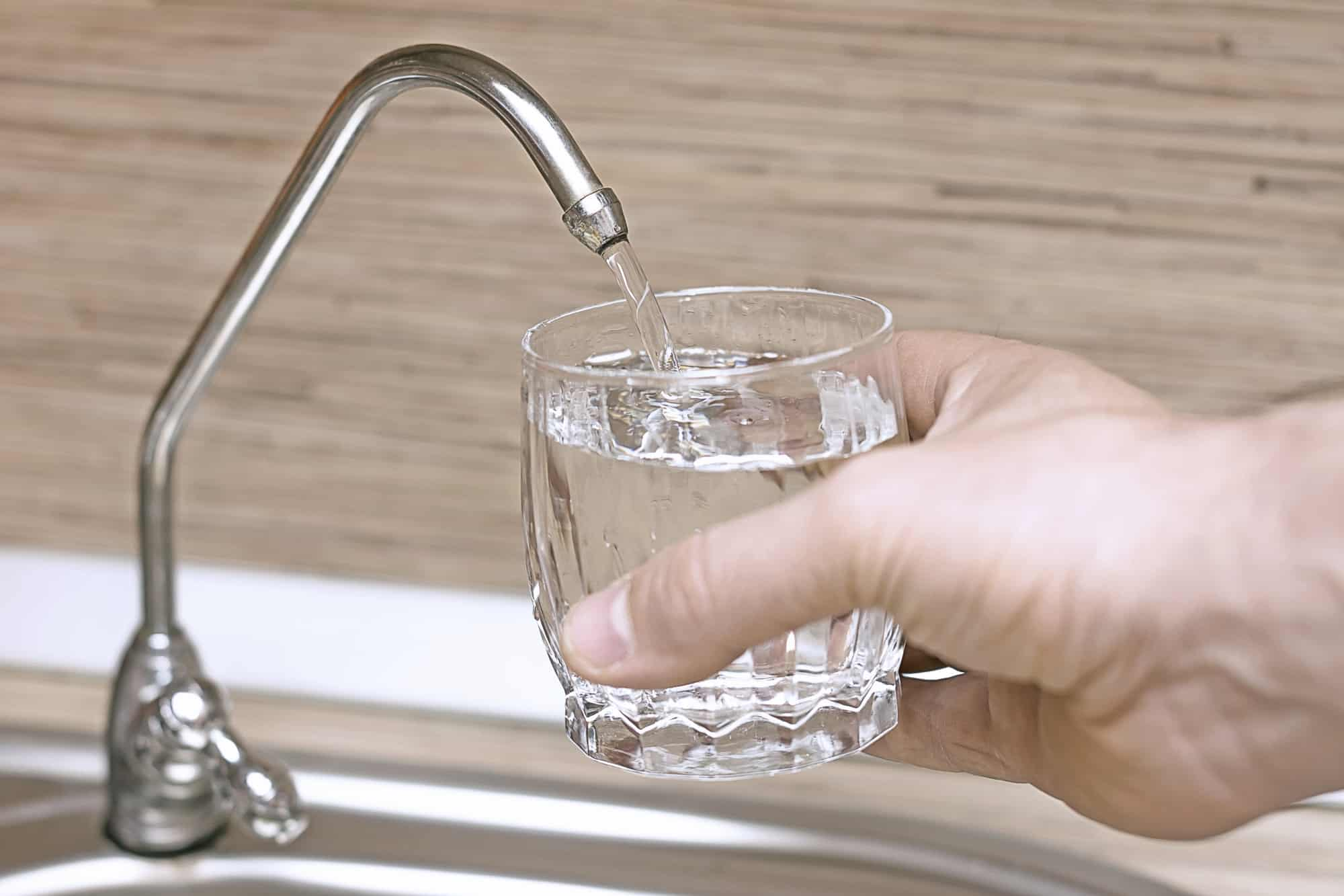 Man holding filling up glass of water at sink