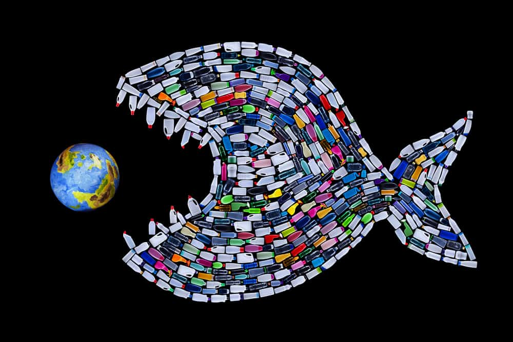 Garbage destroying our world oceans and earth - concept with plastic bottles fish eating the planet