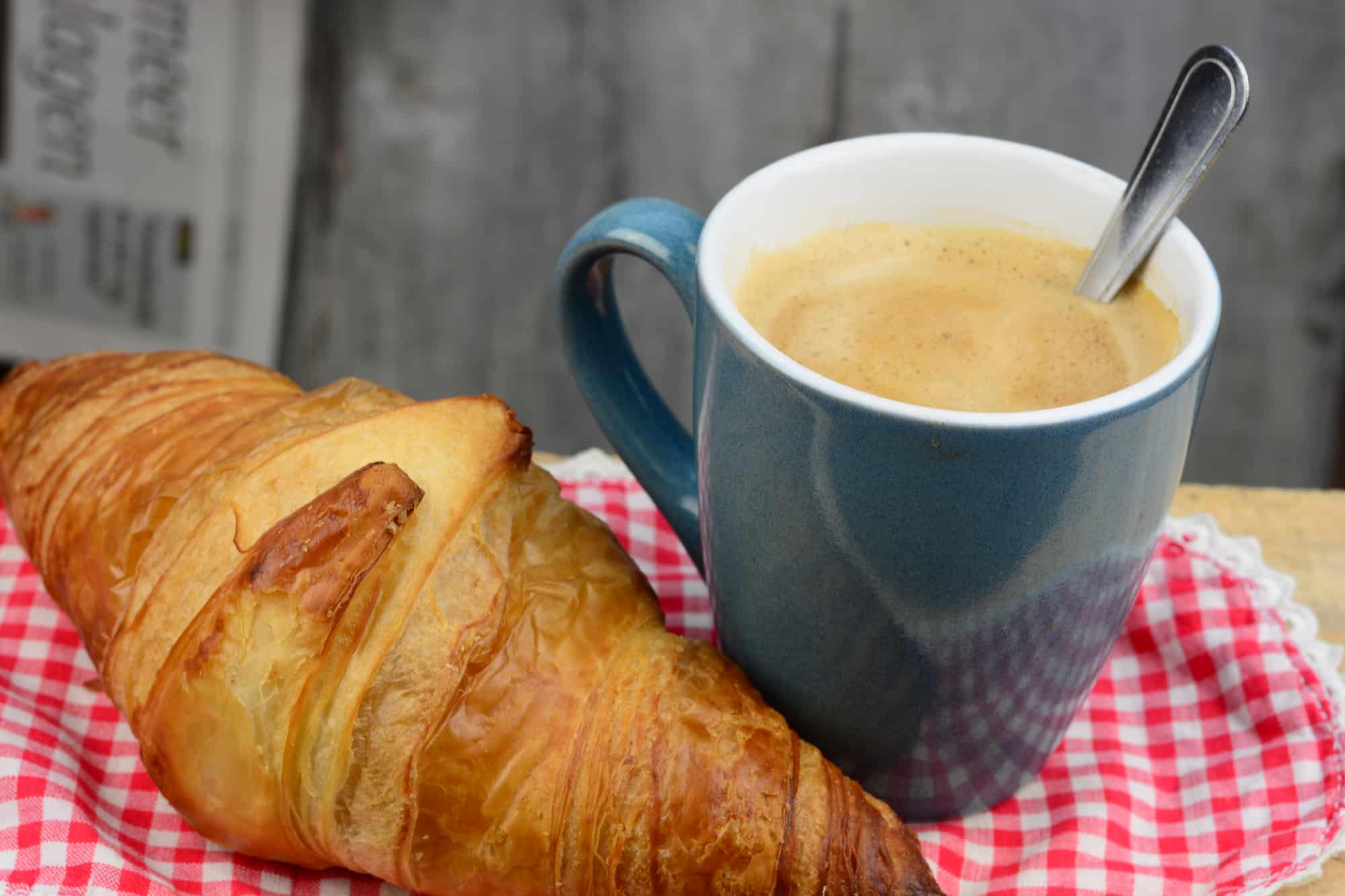 Cafe Latte and croissant on gingham picnic tablecloth