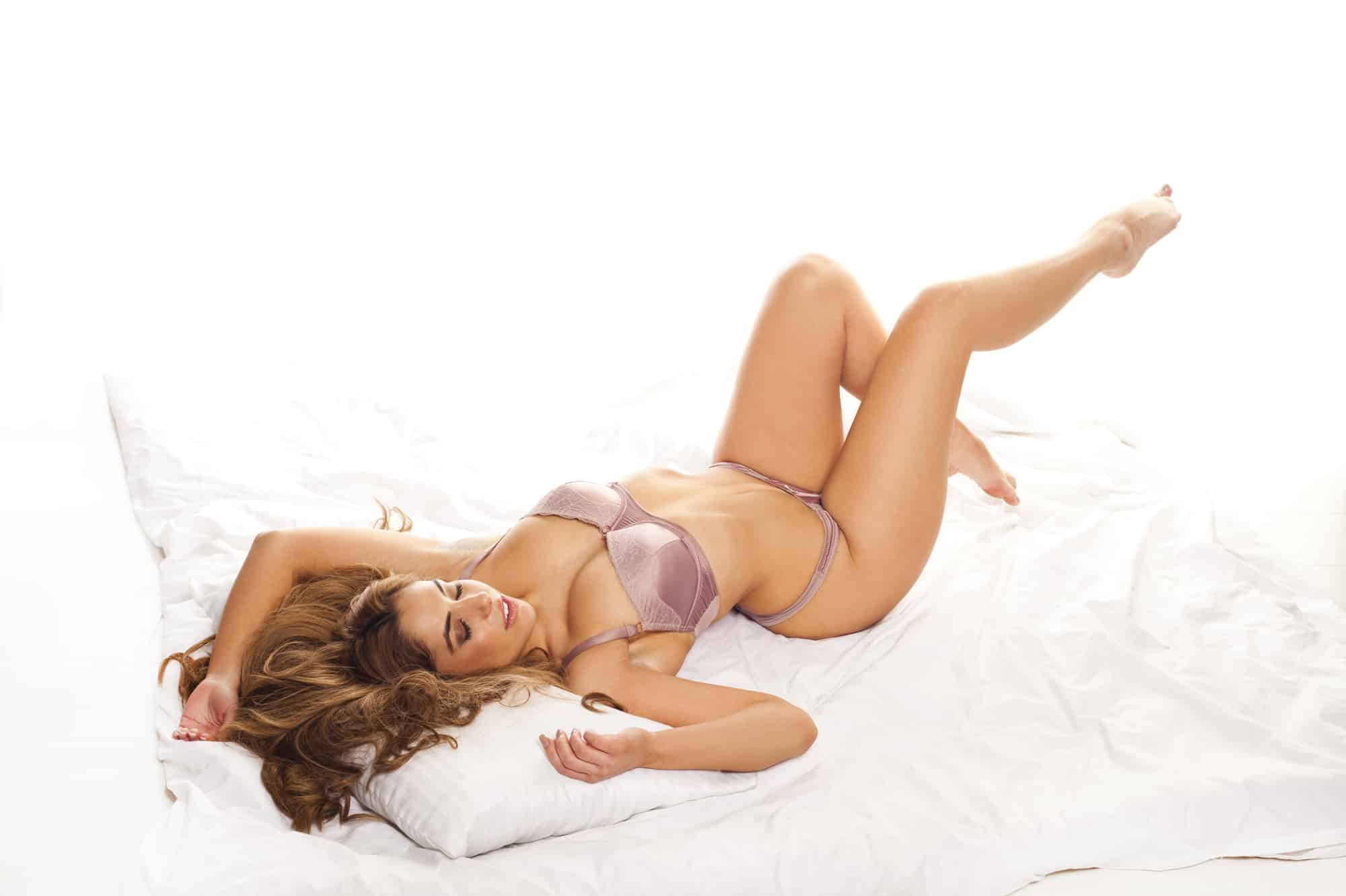 Beautiful curvy woman in lingerie posing on her back on a bed with her long brunette hair