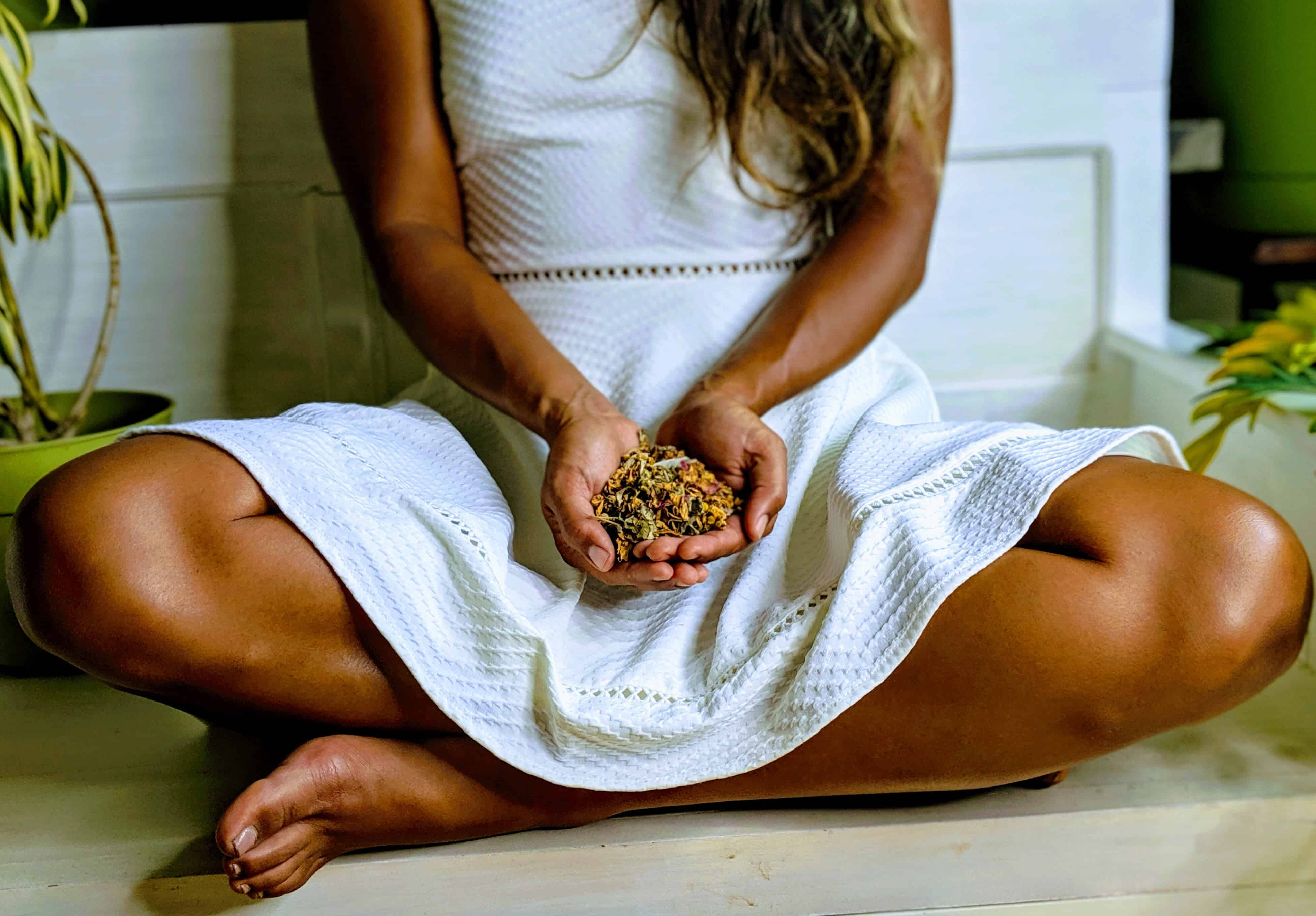 woman sitting in white dress with organic herbs for vaginal steaming
