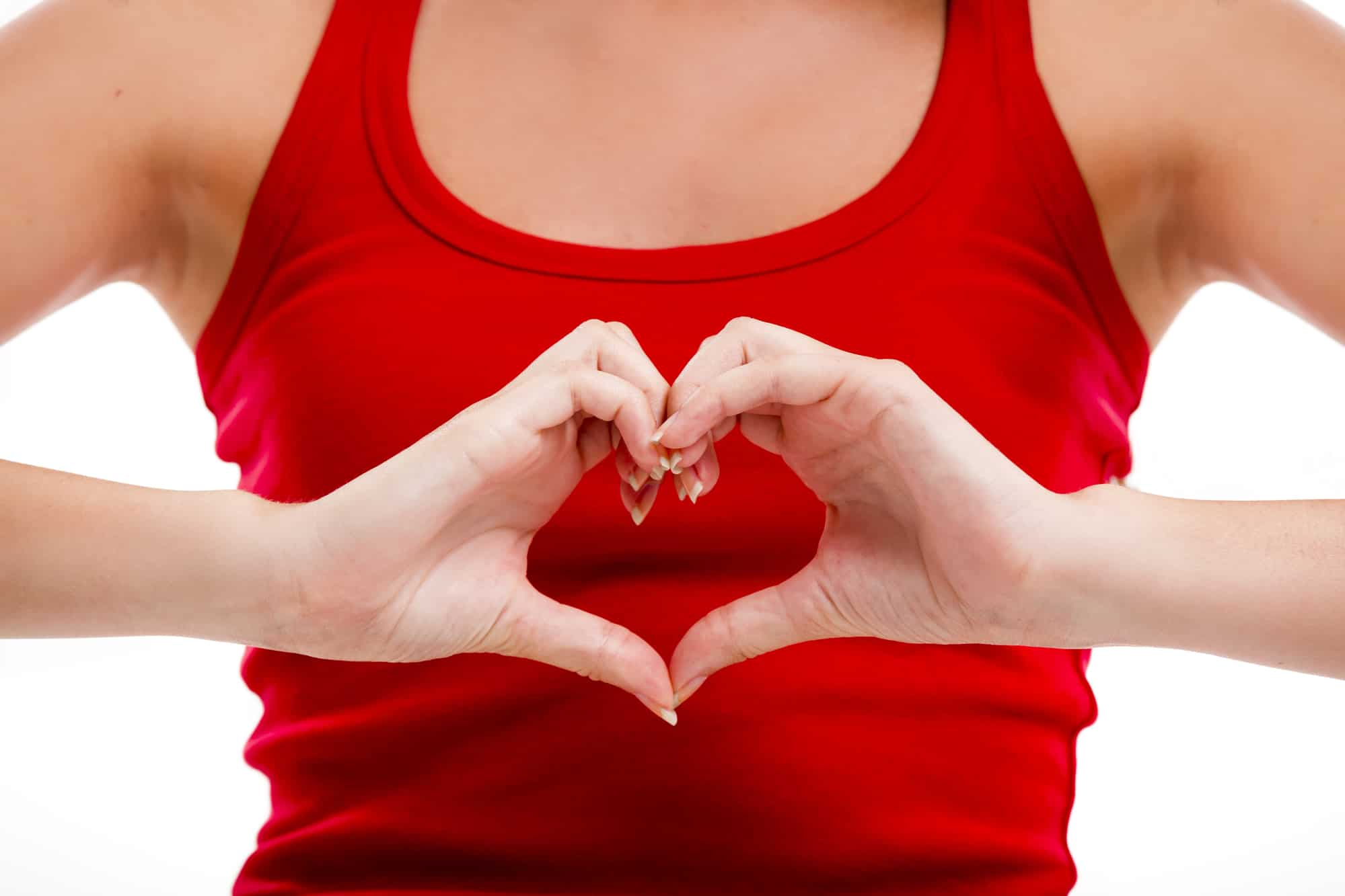 Beautiful young woman over a white background doing a heart shape with her hands
