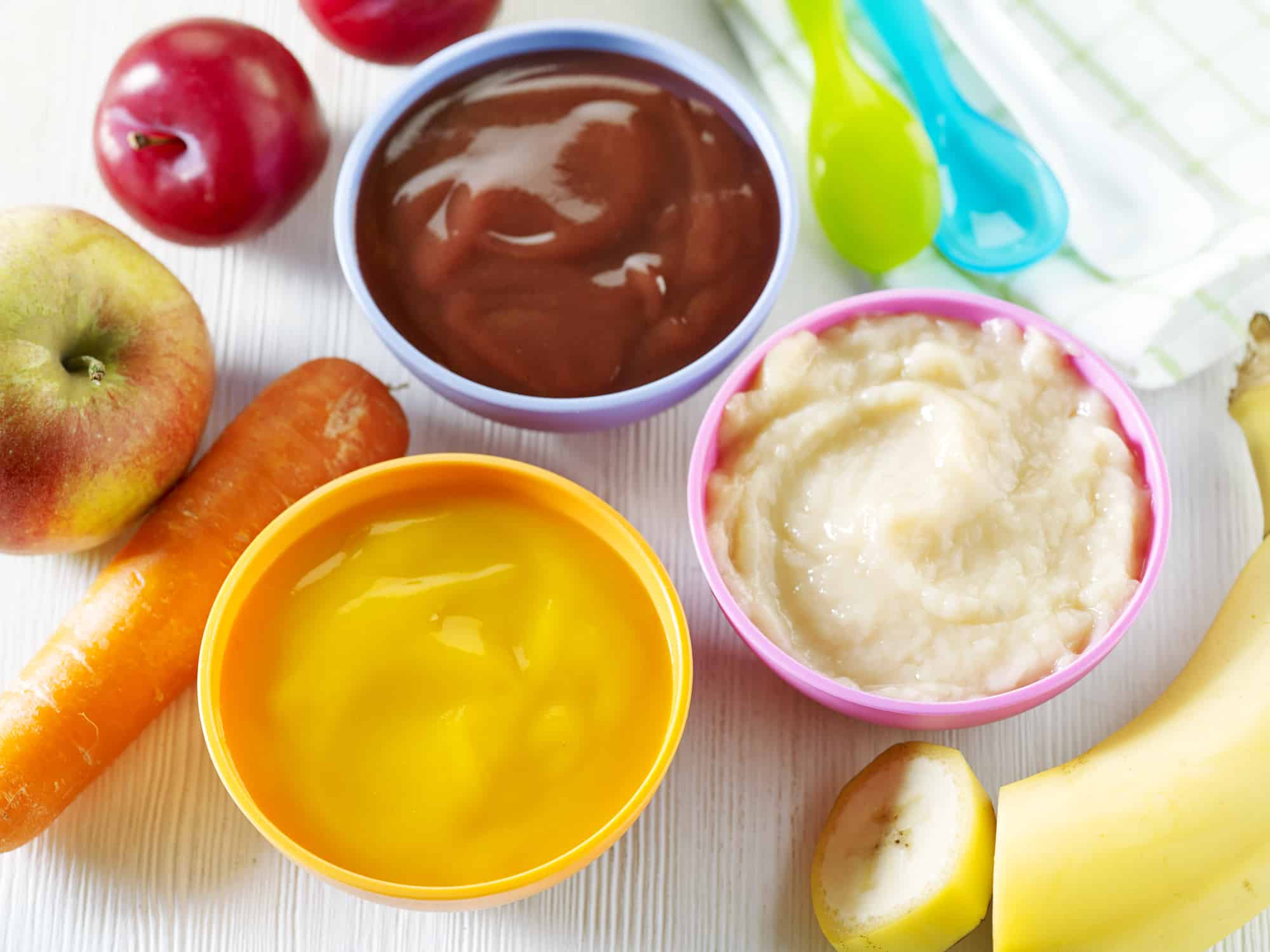 various kinds of baby food in plastic bowls, top view