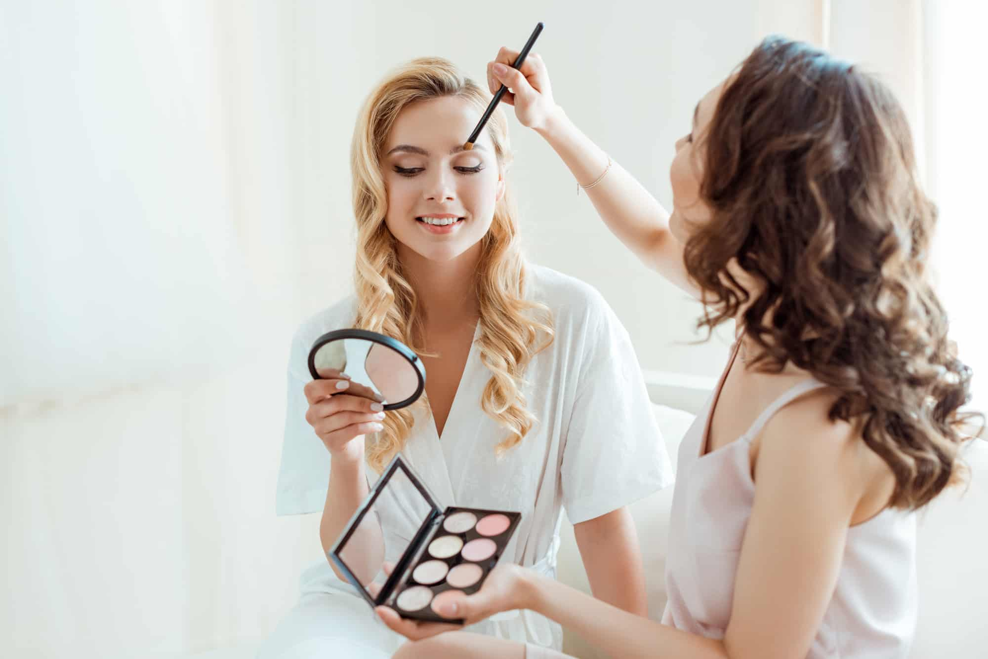 blonde woman having natural makeup applied