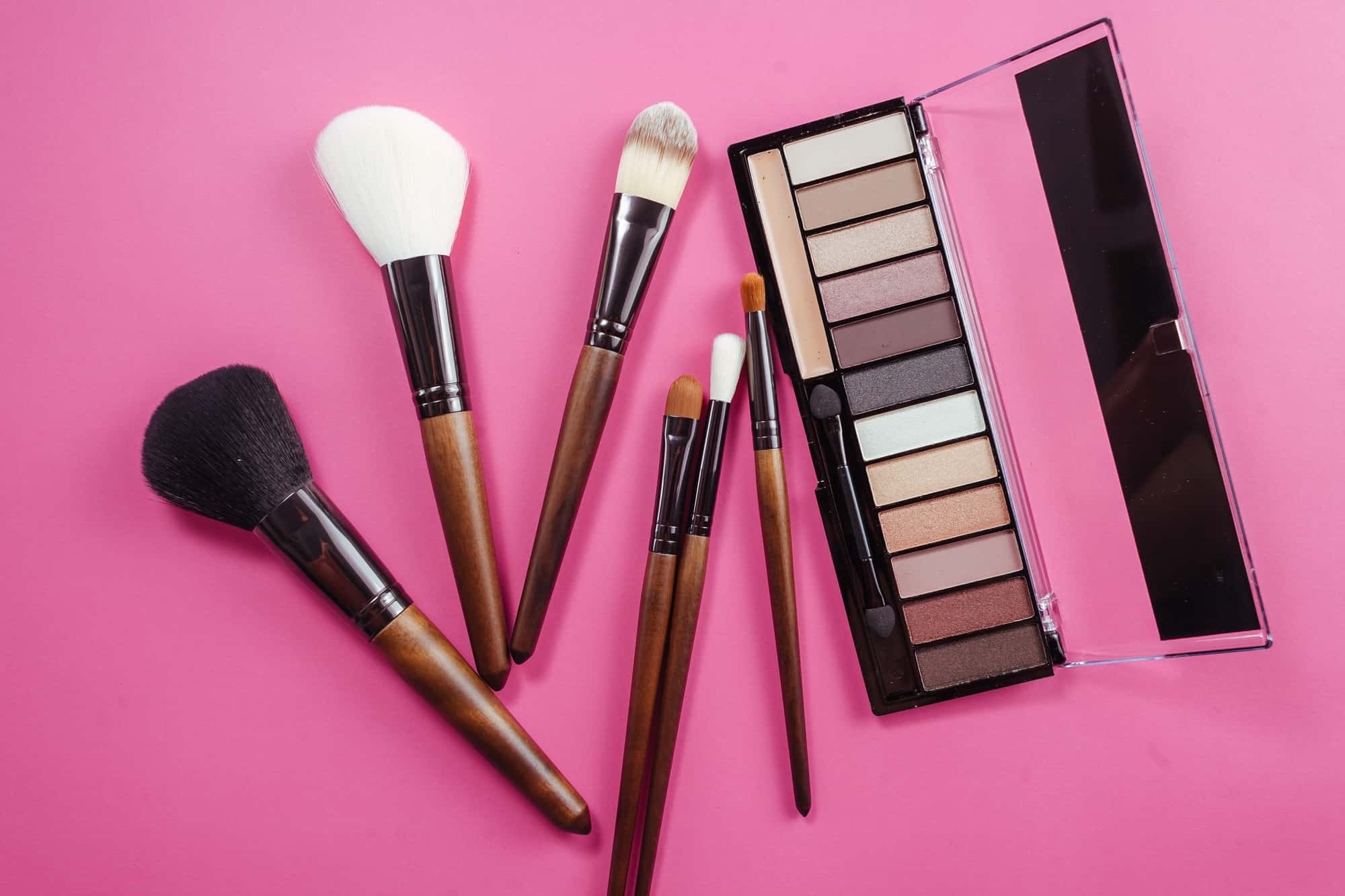 Set of colorful cosmetics on pink background