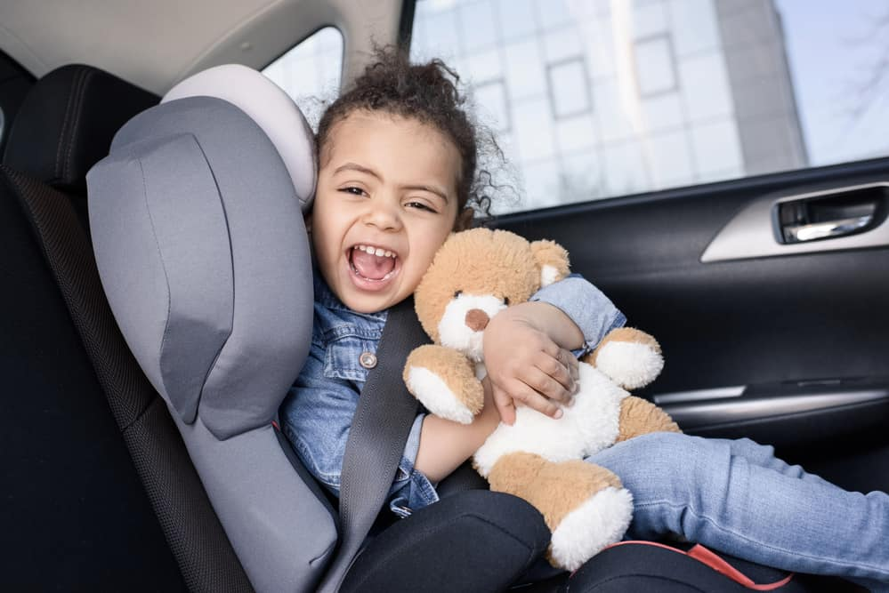Cute young girl hugging bear in her car seat