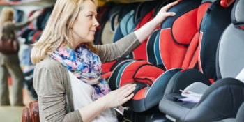 woman choosing child car seat for newborn baby in shop