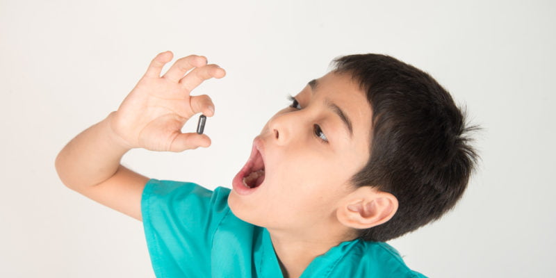 Giving kids medicine, boy try to swallow pills