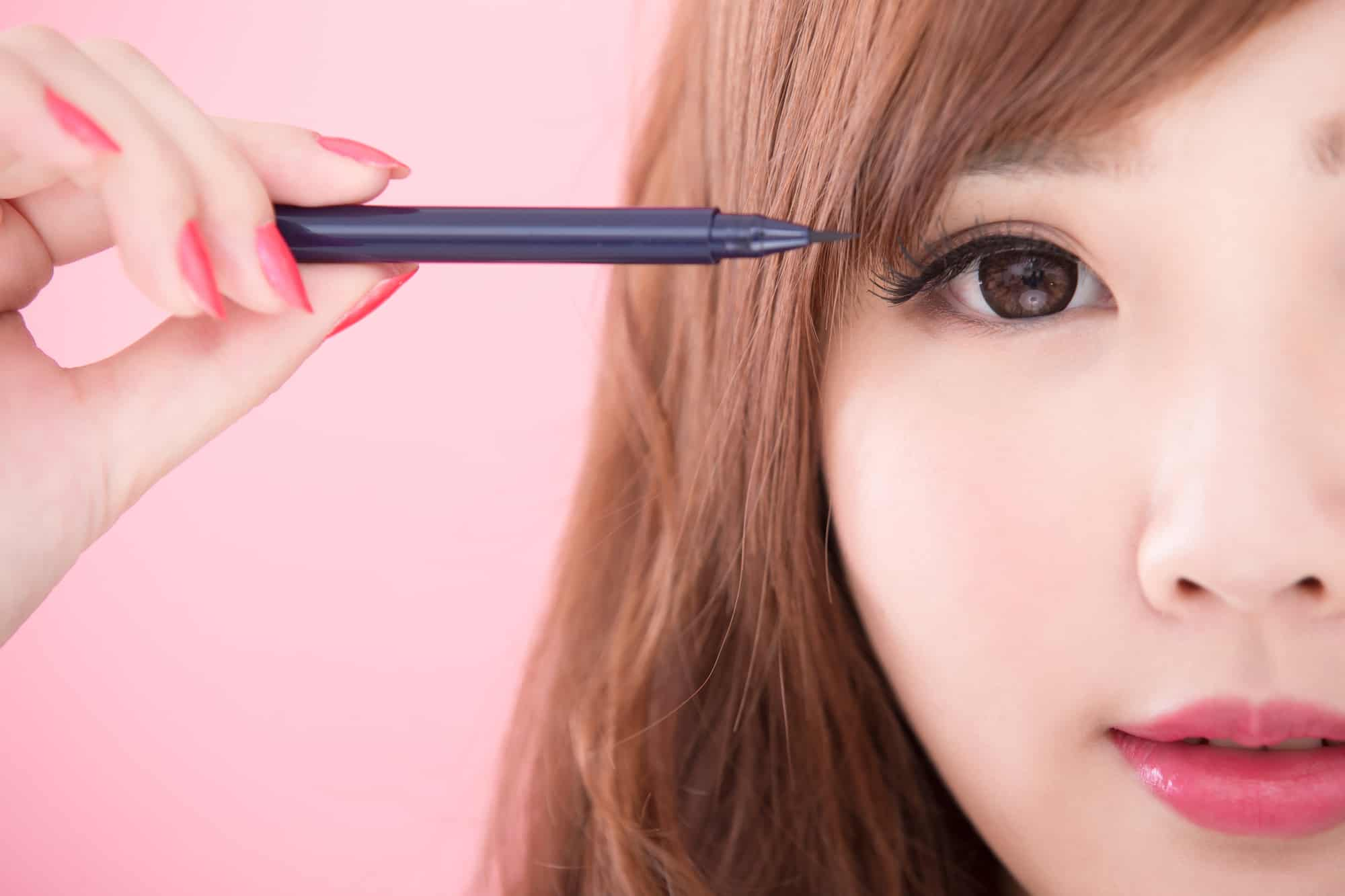 beasian woman puts on eyeliner with pink background