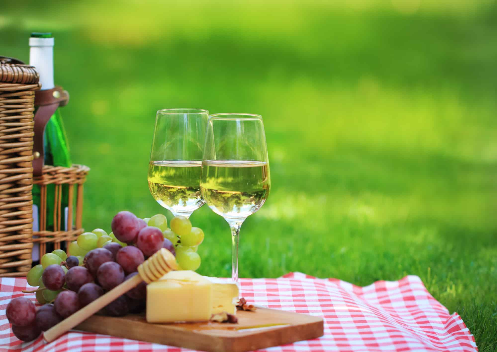 Various sorts of cheese, grapes and two glasses of the white wine