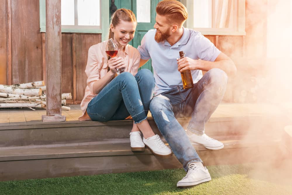 couple drinking on steps outside in summer