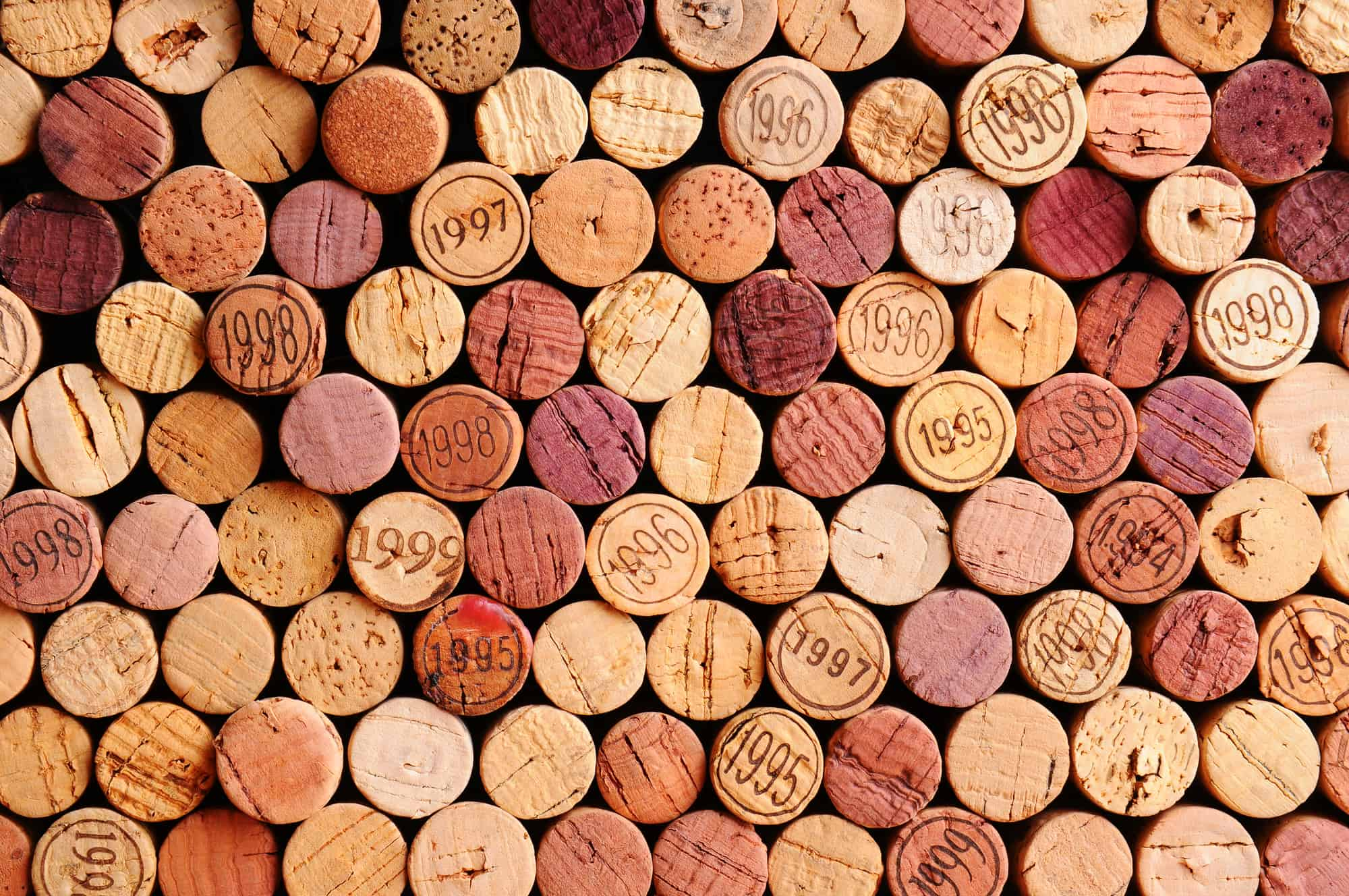 Closeup of a wall of used wine corks. A random selection of use wine corks, some with vintage years. Horizontal format that fills the frame